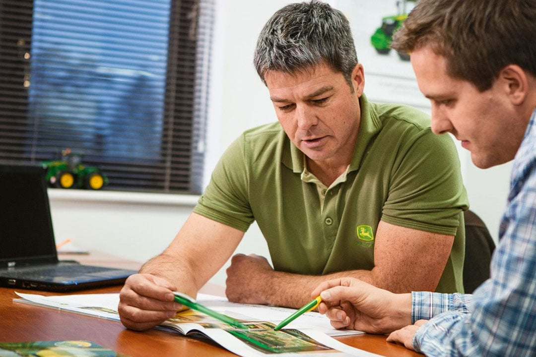 Two men discussing John Deere engines
