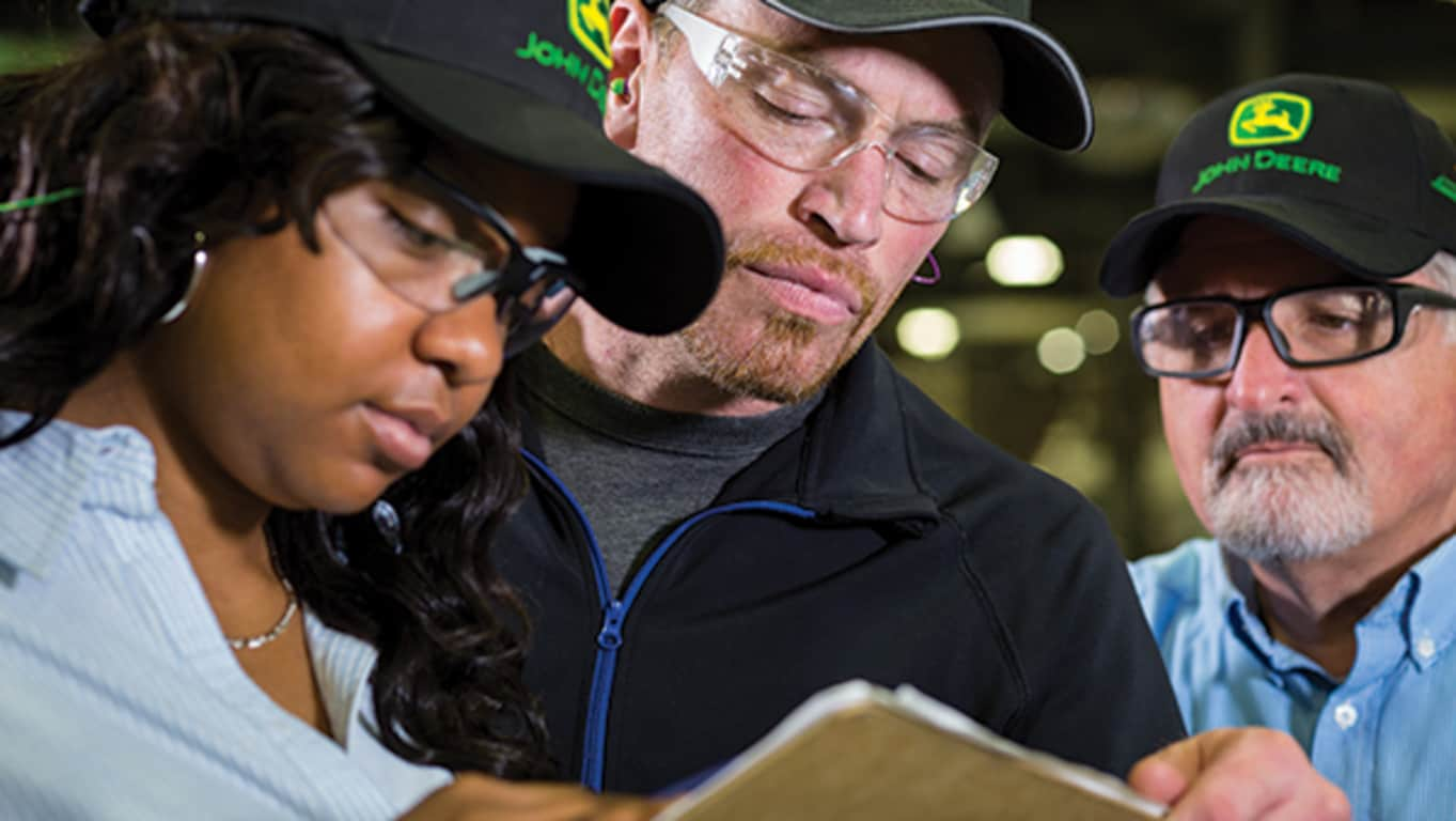 A group of John Deere employees wearing protective eye wear review a clipboard