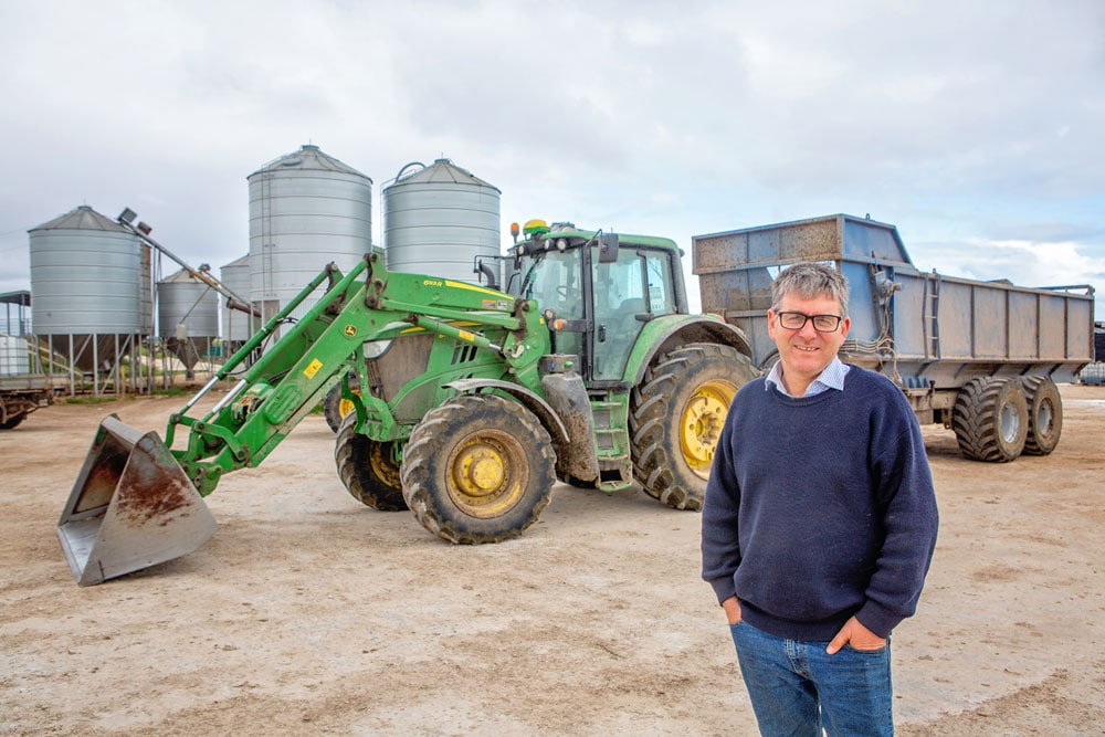 Dairy farmer in front of John Deere equipment