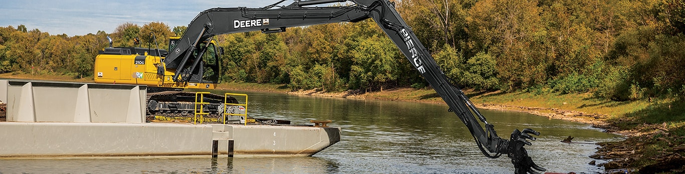 A John Deere excavator works on a barge to clean up the waters