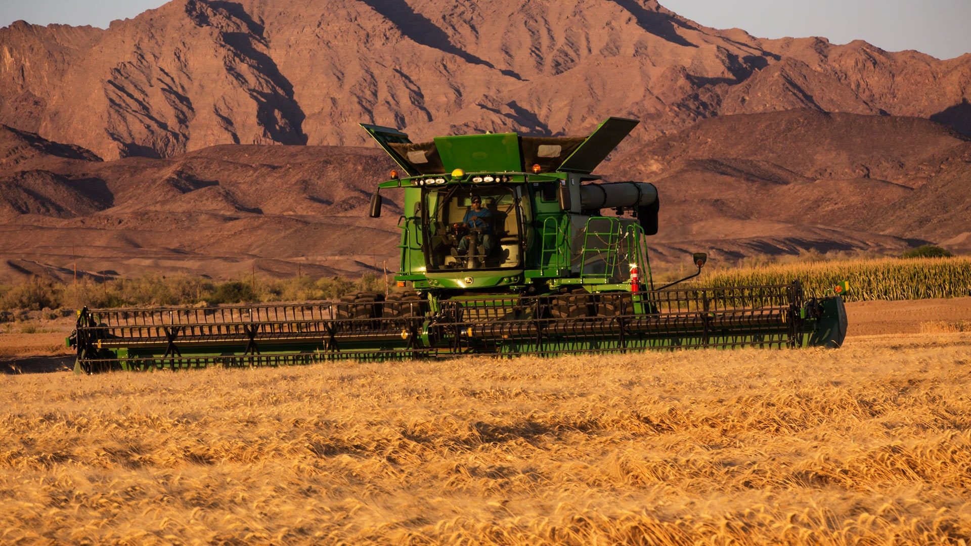 draper platform image of machine moving through field with mountains in background