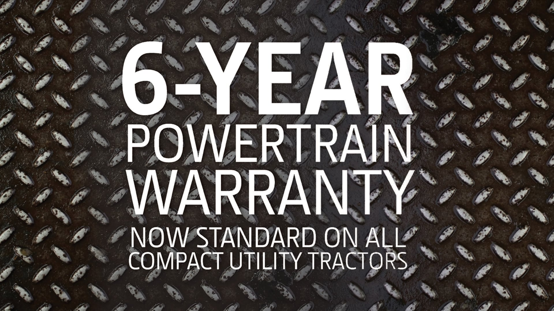 "Text on a metal background that says ""6-Year Powertrain Warranty Now standard on all compact utility tractors"""